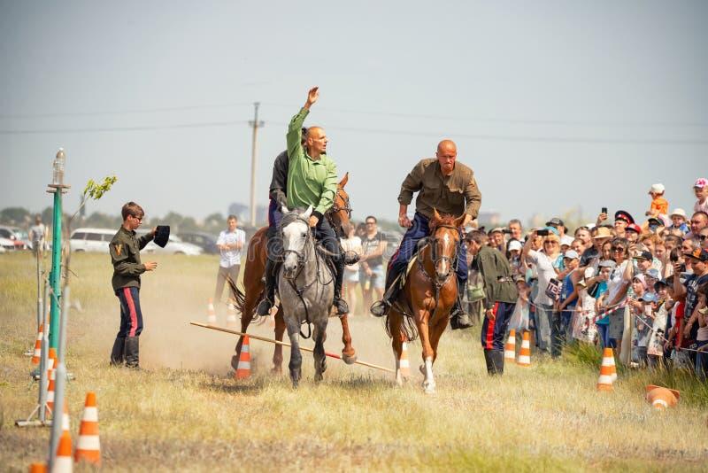 Demonstração da capacidade dos cossacos dos representantes para ficar na sela e para executar a cavalo truques fotografia de stock