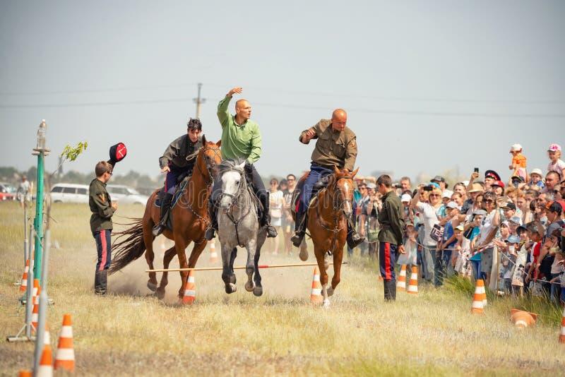 Demonstração da capacidade dos cossacos dos representantes para ficar na sela e para executar a cavalo truques imagem de stock