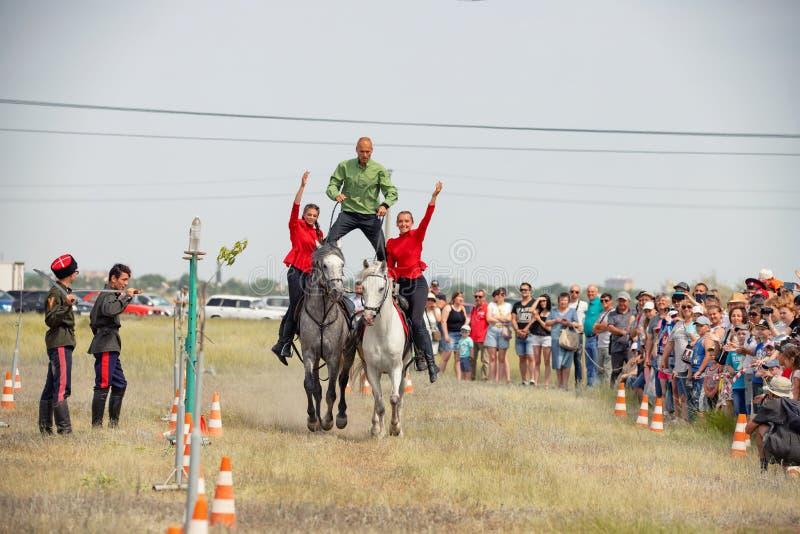 Demonstração da capacidade dos cossacos dos representantes para ficar na sela e para executar a cavalo truques foto de stock