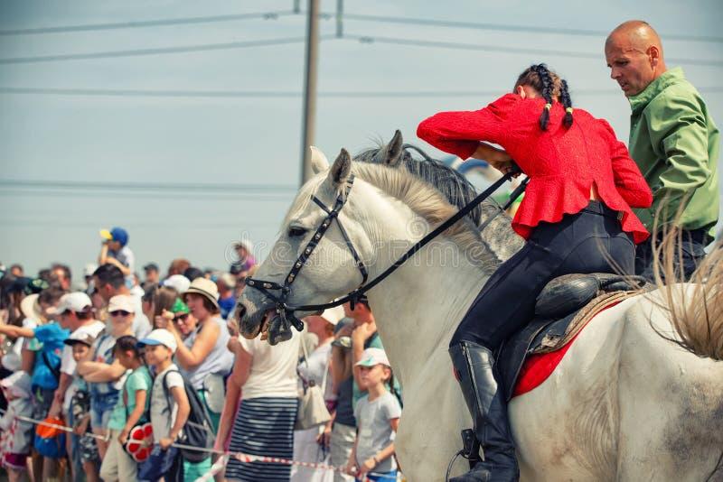 Demonstração da capacidade dos cossacos dos representantes para ficar na sela e para executar a cavalo truques fotos de stock