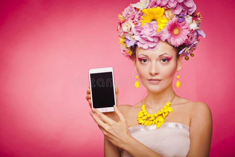 Demonstração de Smartphone app pela mulher nas flores foto de stock