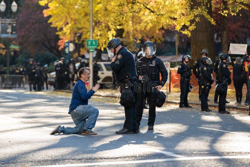 Demonstrador em Portland do centro em seus joelhos no meio de uma rua fotos de stock royalty free