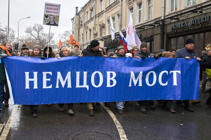 Demonstradores que levam uma bandeira grande: Ponte de Nemtsov no março da memória de Nemtsov em Moscou imagens de stock royalty free