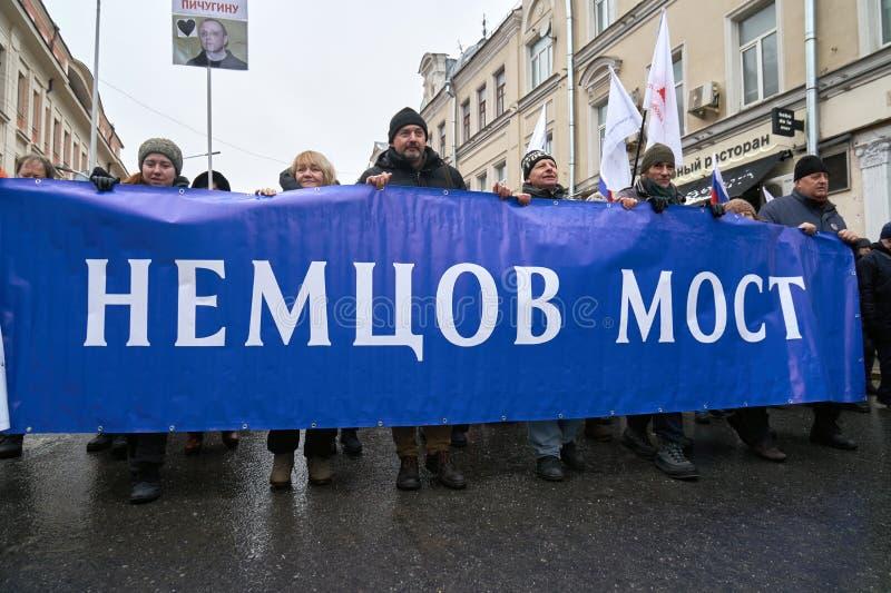 Demonstradores que levam uma bandeira grande: Ponte de Nemtsov no março da memória de Nemtsov em Moscou foto de stock