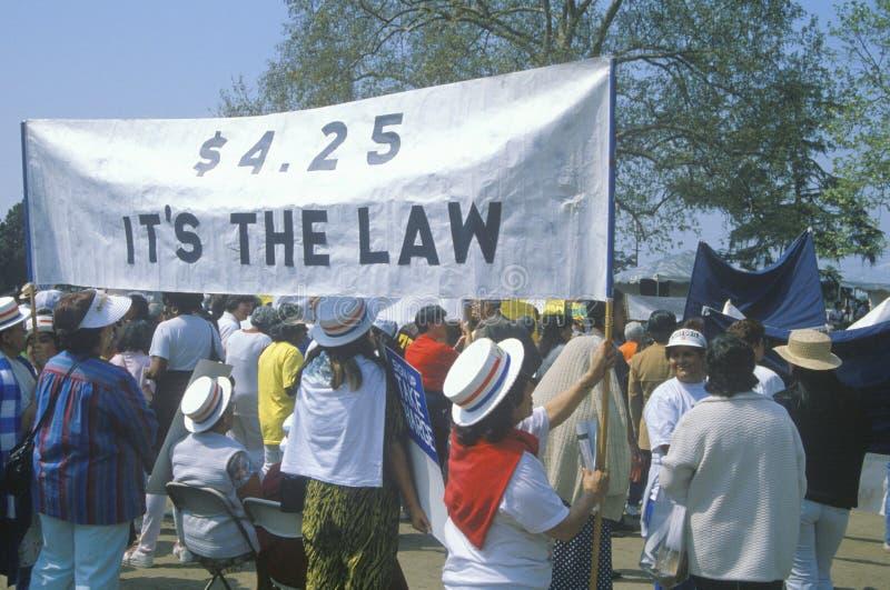 Demonstradores que sustentam a bandeira para leis laborais fotografia de stock