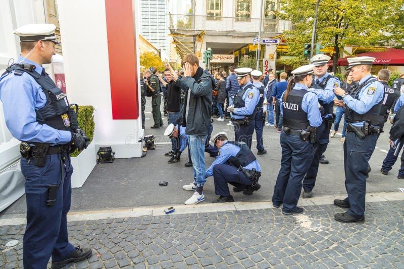 Demonstrant wordt gecontroleerd door politie bij 25ste verjaardag van Duits U stock afbeeldingen