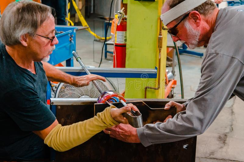 Demonstrating how to shape molten glass into a dish at ArtHop in Kalamazoo Michigan. During winter time stock photos