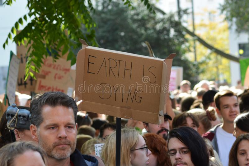 Demonstration during Global Climate Strike with cardboard banner held up saying `Earth is dying` stock photo