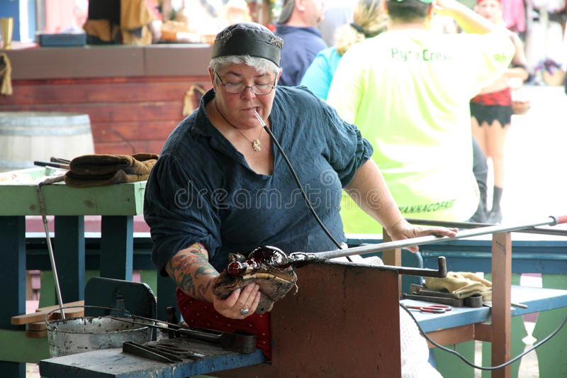 Demonstration of making a cup from a molten glass. KENOSHA, WI - SEPTEMBER 4: Demonstration of making a cup from a molten glass at the annual Bristol Renaissance royalty free stock photos