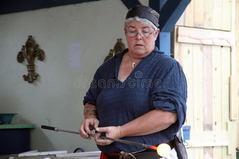 Demonstration of making a cup from a molten glass. KENOSHA, WI - SEPTEMBER 4: Demonstration of making a cup from a molten glass at the annual Bristol Renaissance royalty free stock images