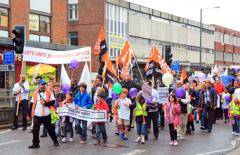 Demonstration march by crowd. A crowd of people demonstrating by walking the streets carrying placards, banners and flags. this was in Bedford, united kingdom
