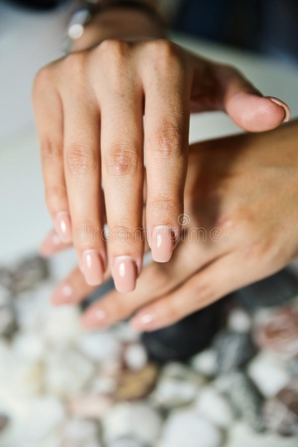 Demonstration of overgrown manicure with gel polish on a gray background royalty free stock images