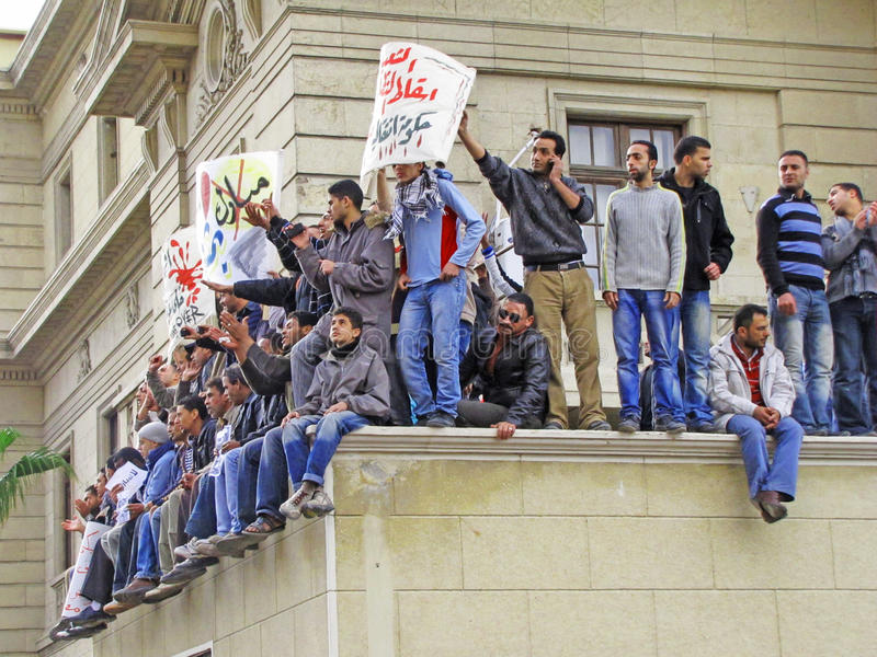 Demonstrators Sitting On A Building Editorial Photo