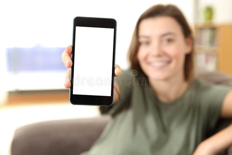 Demostración adolescente una pantalla elegante en blanco del teléfono en una casa foto de archivo libre de regalías