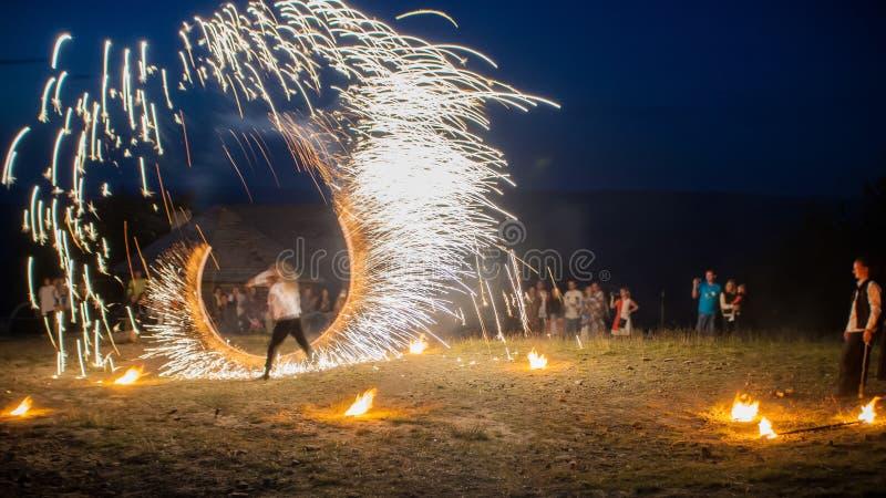 Demostración asombrosa del fuego con fuegos artificiales línea semicircular de la U-forma con muchas chispas Y audiencia admirati imagen de archivo libre de regalías