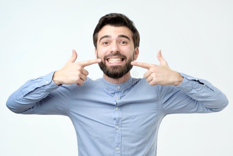 Demostración confiada sonriente del hombre hispánico y el señalar con los dientes y la boca de los fingeres foto de archivo