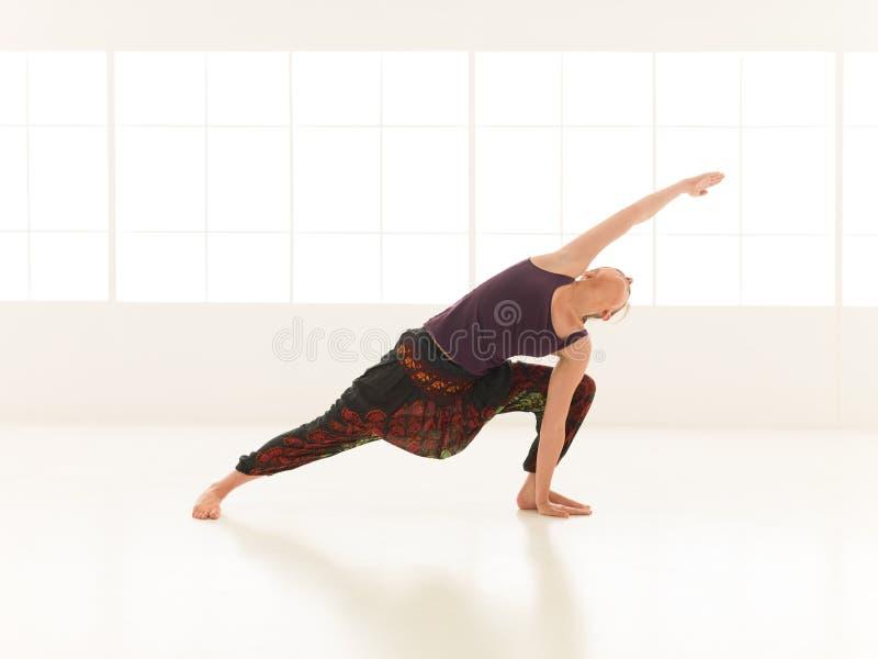 Demostración de la actitud avanzada de la yoga de la mujer atractiva joven imagen de archivo libre de regalías
