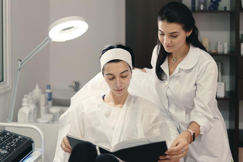 Demostración del Cosmetologist a sus innovaciones pacientes en cosmetología fotografía de archivo