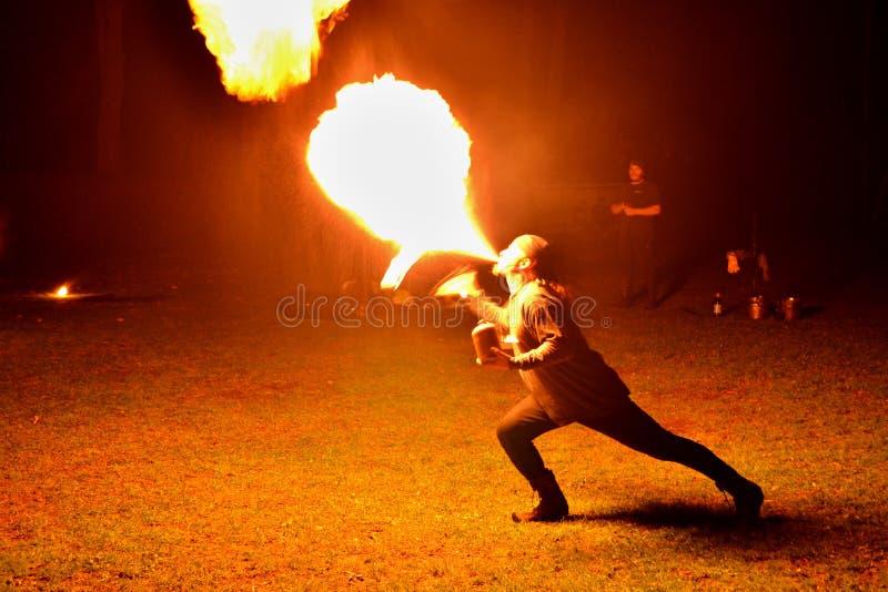 Demostración del fuego - artista que escupe hacia fuera el fuego en la oscuridad foto de archivo libre de regalías