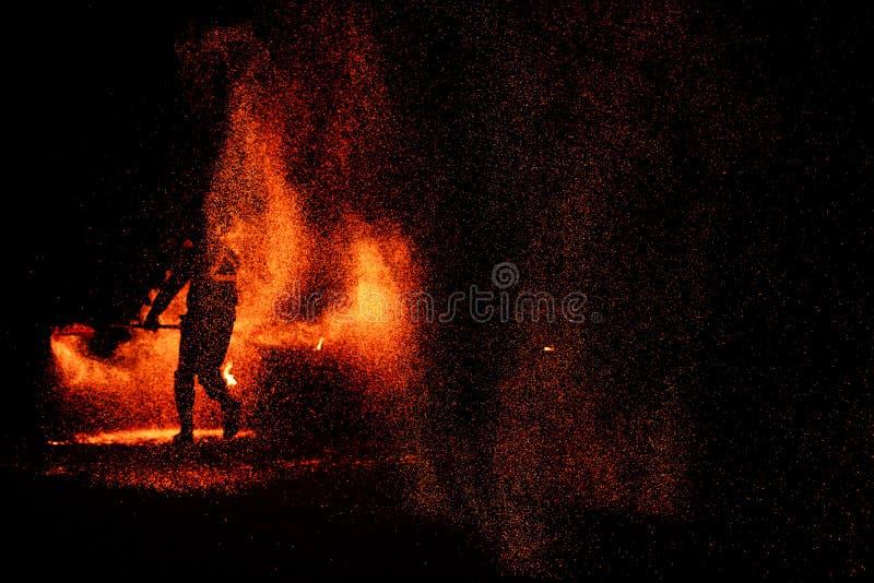 Demostración del fuego, bailando con la llama, amo masculino que hace juegos malabares con los fuegos artificiales, funcionamient imagenes de archivo
