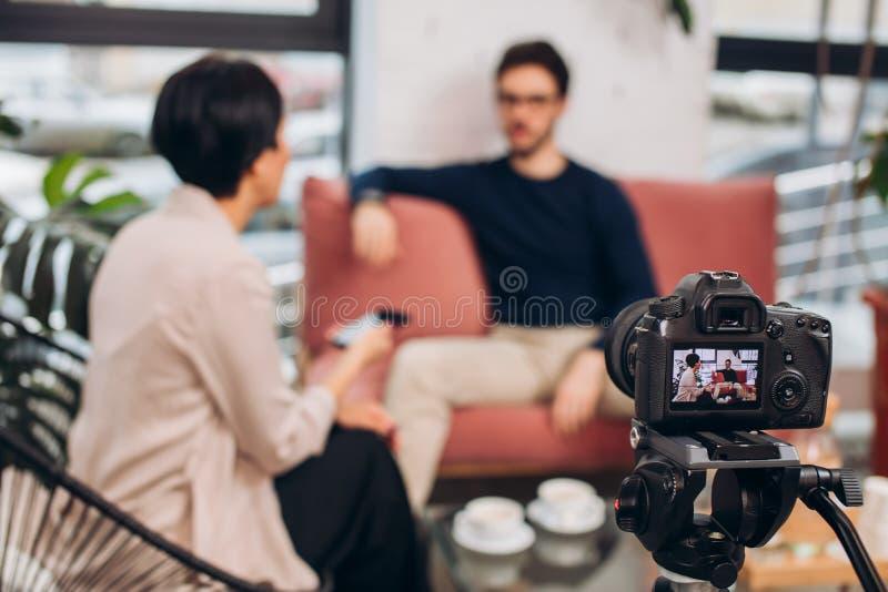 Demostración en línea programa de la vida cámara que registra la charla entre una mujer y un individuo imagen de archivo libre de regalías