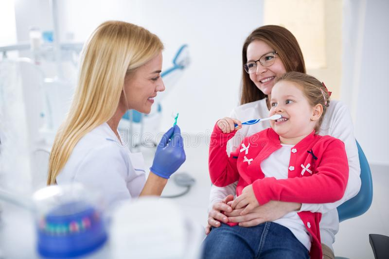 Demostración femenina joven del dentista cómo lavar los dientes fotografía de archivo