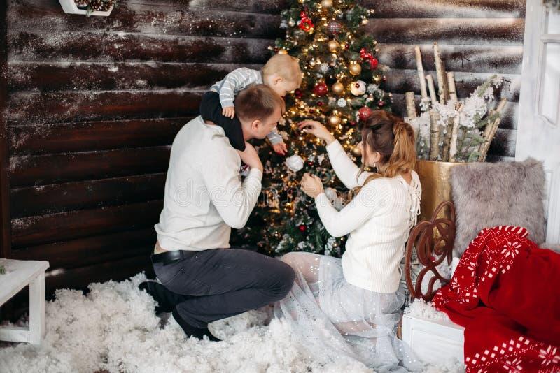 Demostración hermosa y elegante cómo adorna el árbol de navidad poco para el hijo imagenes de archivo