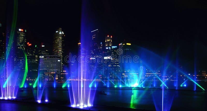 Demostración moderna de la fuente del verde azul en el mar y arquitecturas abstractas y horizonte de la noche en Singapur fotos de archivo