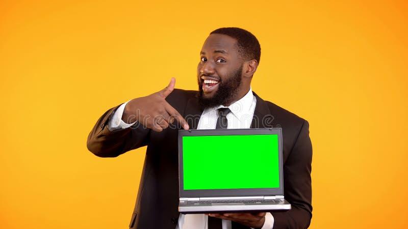 Demostraci?n negra alegre del encargado en el ordenador port?til prekeyed, lugar para el anuncio imagen de archivo libre de regalías