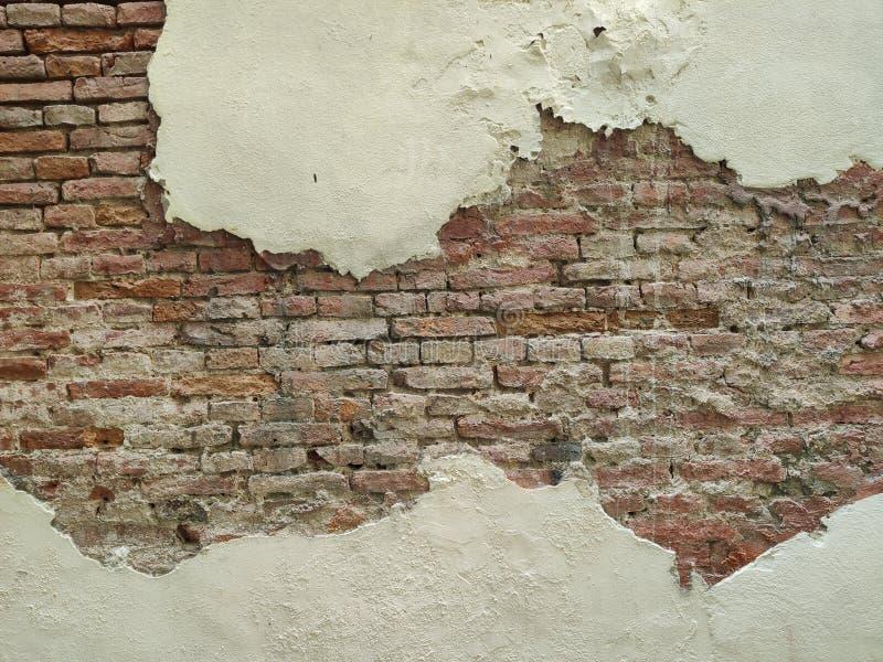 Demostración que se agrieta de la vieja superficie de la pared dentro del ladrillo rojo fotografía de archivo libre de regalías