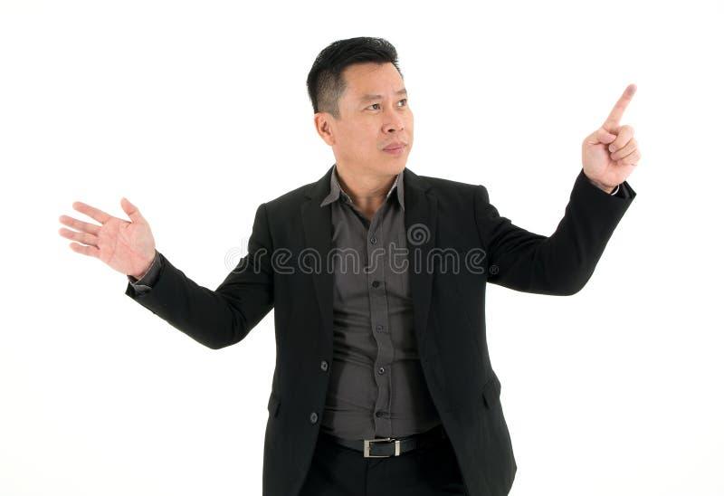 Demostración sonriente y perno del hombre de negocios que señalan en algo aislado en el fondo blanco fotos de archivo libres de regalías
