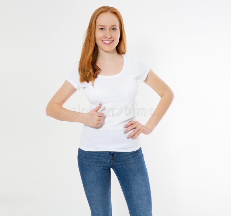 Demostraci?n roja hermosa de la muchacha del pelo como muestra en una camiseta blanca aislada Mujer principal roja de la sonrisa  fotos de archivo libres de regalías