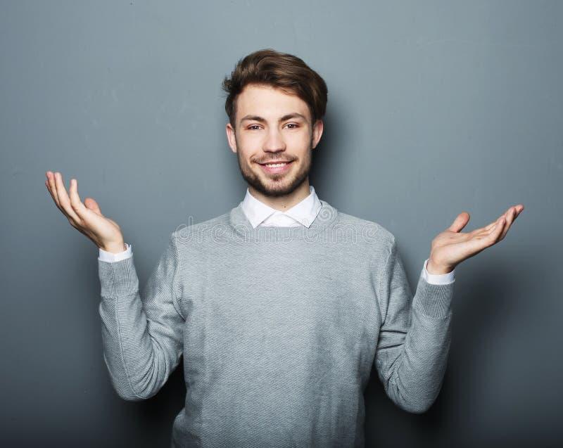 Demostraciones felices sonrientes del hombre de negocios de los jóvenes algo imagenes de archivo