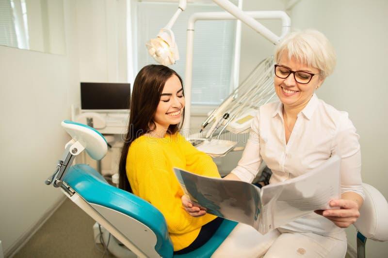 Demostraciones profesionales del doctor a la imagen paciente de dientes sanos en su oficina dental médica Secreto de dientes sano foto de archivo libre de regalías
