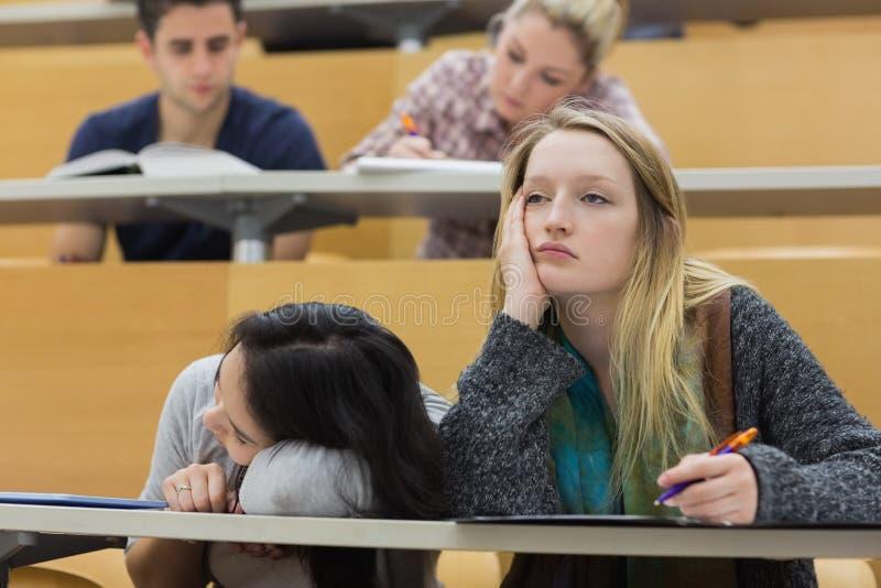 Demotivated studenter i en hörsal royaltyfri foto