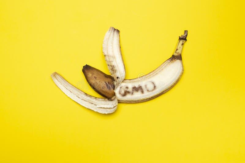 """Den övermogna svärtade bananen med en delvist skalad hud och ord""""GMO""""en som är skriftlig på trämassan, är på en gul bakgrund arkivbild"""