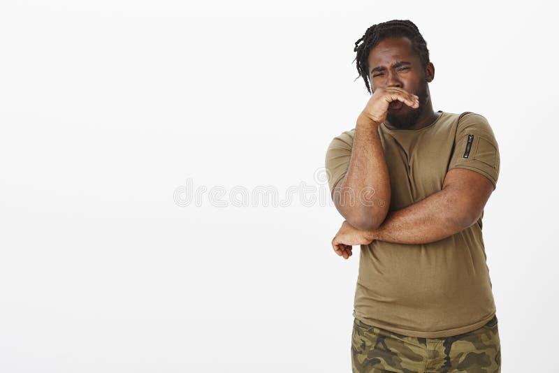 Den äcklade olyckliga mörkhyade mannen i militär dräkt, den täckande näsan med gömma i handflatan från stank eller den fruktansvä royaltyfria foton