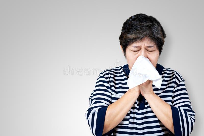 Den äldre asiatiska kvinnan har influensa och nyser från säsongsbetonat virusproblem för sjukdom arkivfoton