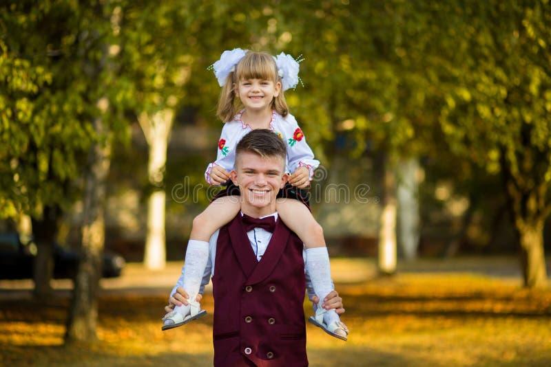 Den äldre brodern och den mer unga systern går i höst parkerar i skolalikformig royaltyfria bilder