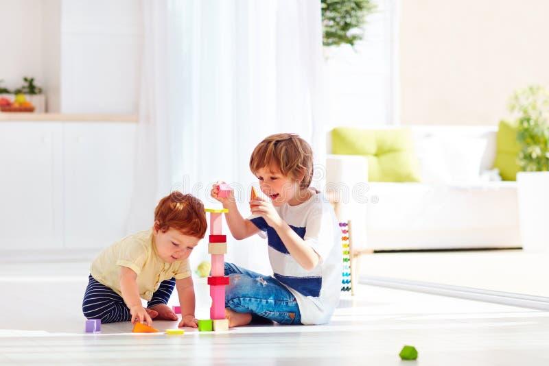Den äldre brodern som spelar med junior, behandla som ett barn pojken hemma royaltyfria bilder