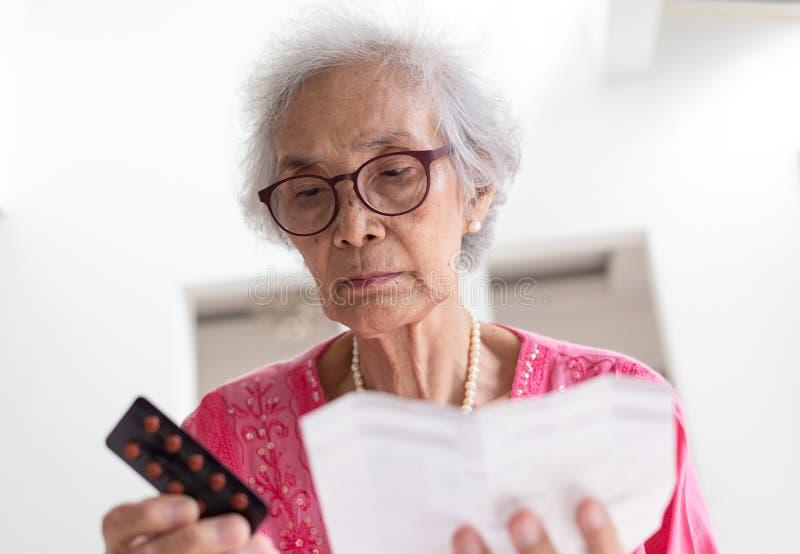 Den äldre caucasian kvinnan med medicin och läsning förgiftar föreskrift arkivfoton