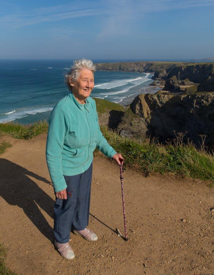 Den äldre damen i hennes eighties med att gå är lojal mot härlig kustplats med vind som blåser till och med hennes hår royaltyfri fotografi