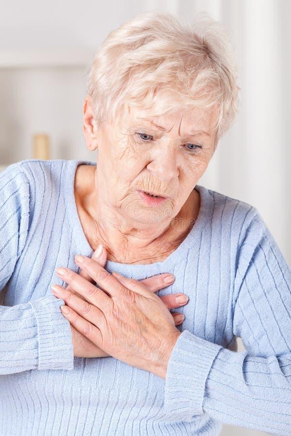 Den äldre damen med bröstkorgen smärtar arkivfoton
