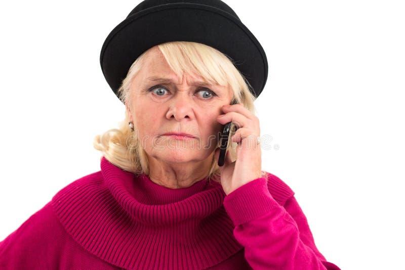 Den äldre damen rymmer mobiltelefonen arkivbild
