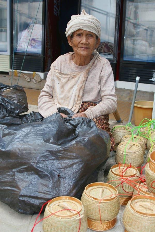 Den äldre försäljaren säljer vide- korgar för ris i Vientiane Laos royaltyfria bilder