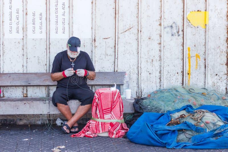 Den äldre fiskaren sitter på stranden och att reparera fiska n arkivfoto