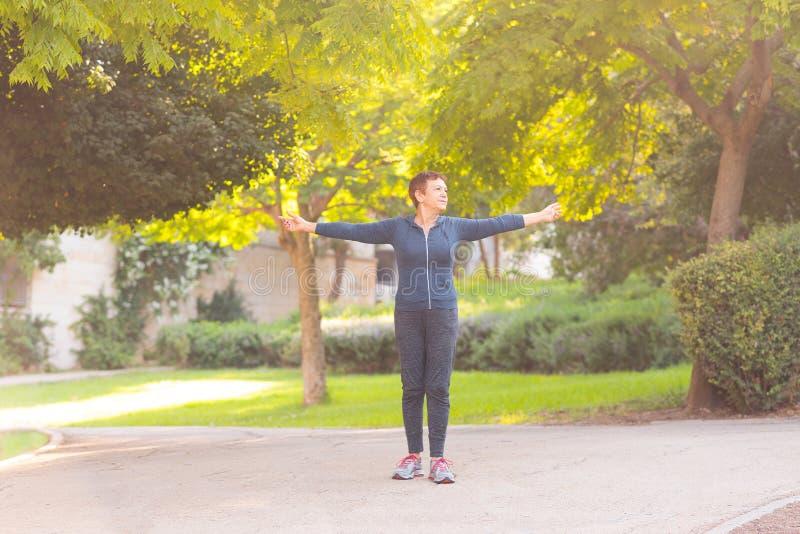 Den äldre härliga aktiva lyckliga kvinnan i morgonen i hösten parkerar att göra sportövningar royaltyfria foton