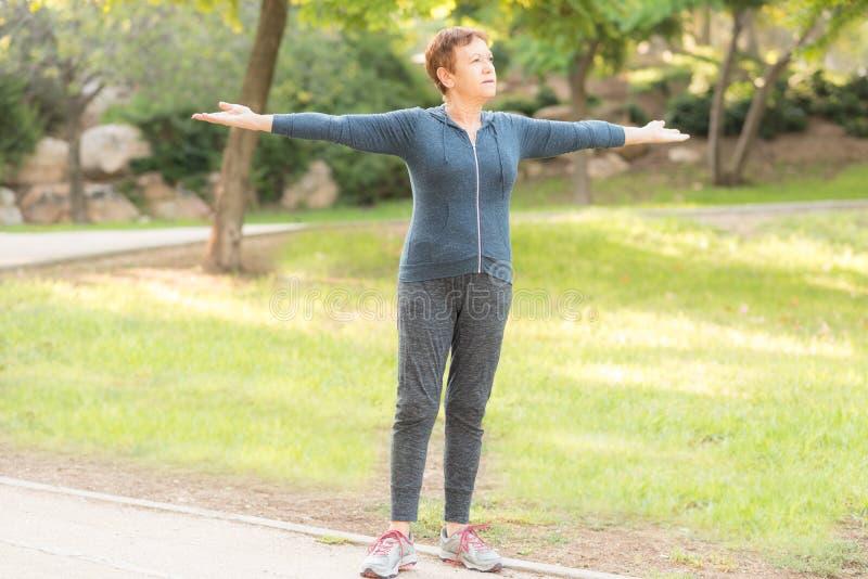 Den äldre härliga aktiva lyckliga kvinnan i morgonen i hösten parkerar att göra sportövningar royaltyfria bilder