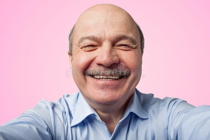 Den äldre höga mannen med en mustasch som rymmer en smartphone och, gör selfie royaltyfri foto