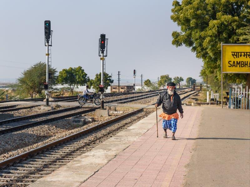 Den äldre indiska mannen promenerar drevplattformen på stationen i Sambhar Rajasthan india royaltyfri bild